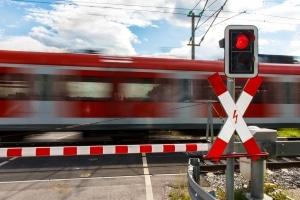 Andreaskreuz mit rotem Blinklicht: Fahrzeuge und Fußgänger müssen warten.
