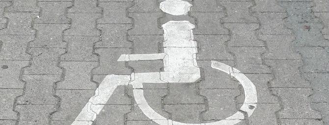 Ein Behindertenparkplatz ist unter anderem an die Bedürfnisse von Rollstuhlfahrern angepasst.