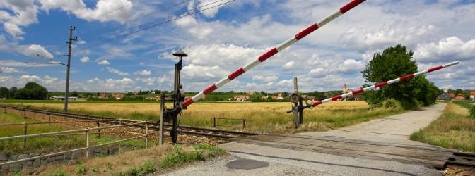 Beschrankter Bahnübergang: Die sich senkenden Schranken weisen darauf hin, dass sich ein Zug nähert.