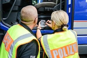 Polizeibeamte nutzen ein Fahrerkarten-Lesegerät um die Daten zu überprüfen.
